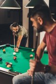 couple of young successful handsome men playing in pool at bar