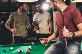 young caucasian men drinking beer beside billiard table in bar