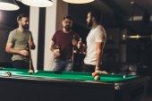 young handsome caucasian men beside billiard table in bar