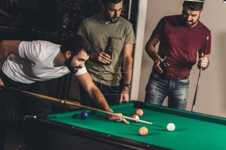 group of young successful handsome men playing in pool at bar