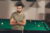 young handsome caucasian man beside billiard table