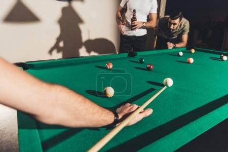cropped image of company of handsome men playing in pool