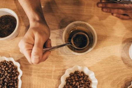 cropped shot of man holding spoon while testing aromatic coffee
