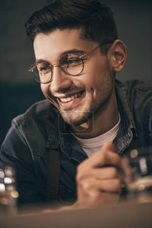 portrait of cheerful man in eyeglasses looking away