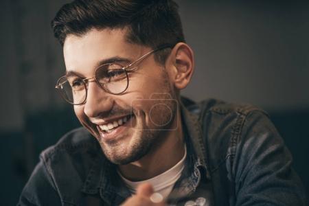 portrait of cheerful man in eyeglasses looking away