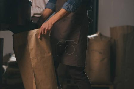 partial view of worker in apron with paper bags of coffee beans