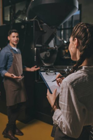selective focus of woman checking colleagues work during coffee roasting process