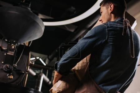back view of coffee roaster holding paper bag in hands while standing at roasting machine