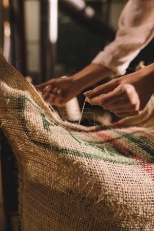 partial view of worker tying sack bag with coffee beans