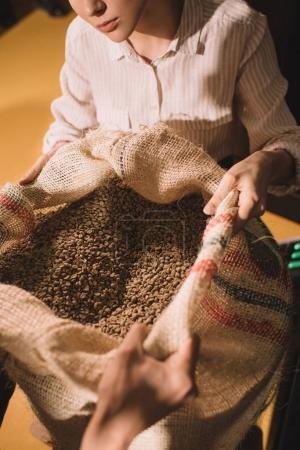 cropped shot of workers holding sack bag with coffee beans together