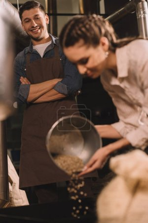 selective focus of woman pouring coffee beans into roasting machine