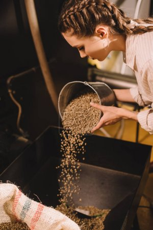 side view of young worker pouring coffee beans into container