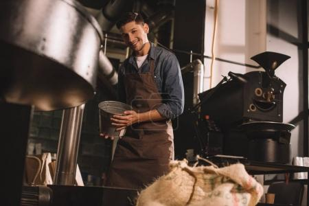 young coffee roaster with metal bucket in hands working in coffee shop