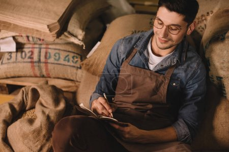 portrait of smiling coffee roaster in eyeglasses and apron making notes in notebook