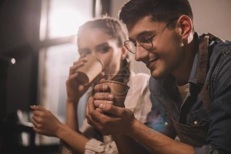 couple with cups of coffee having break during work at coffee shop
