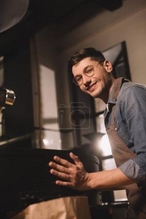 side view of smiling young coffee roaster working in coffee shop