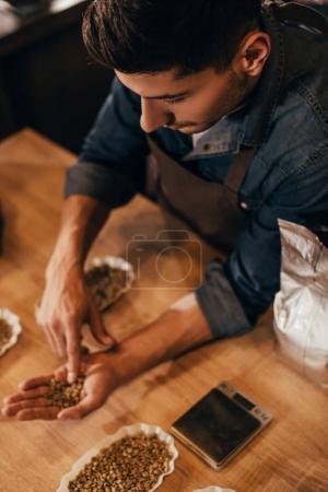 Photo pour Mise au point sélective de l'homme, contrôle de qualité des grains de café à une table en bois - image libre de droit
