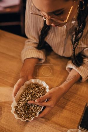 overhead view of young woman testing coffee beans in coffee shop