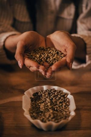 selective focus of woman holding coffee beans in hands