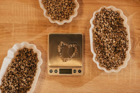 top view of arrangement of bowls with coffee beans for food function and kitchen scales on wooden tabletop