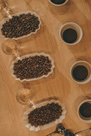 top view of arrangement of bowls with coffee beans and glasses of water for food function on wooden tabletop
