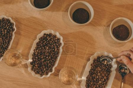 Photo for Flat lay with bowls of grind coffee and coffee beans for food function on wooden surface - Royalty Free Image