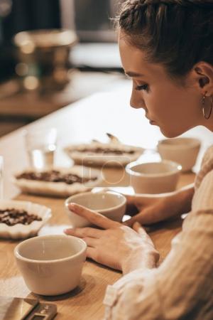 Photo pour Vue latérale de la jeune femme test de grains de café en café-restaurant - image libre de droit