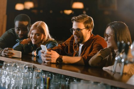 company of young people using smartphones at bar