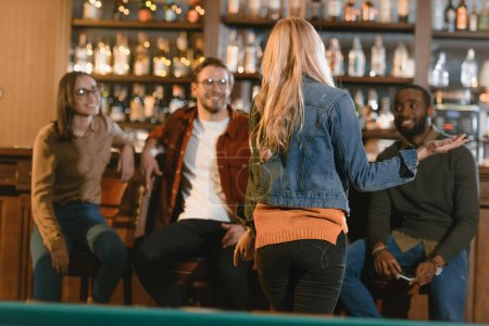 back view of young girl at bar with friends