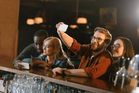 company of attractive young friends taking selfie at bar