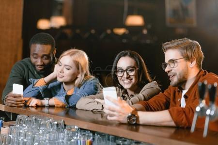 young attractive company at bar looking at smartphones screen