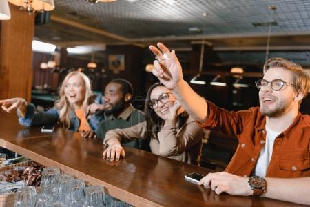 Photo pour Les jeunes au comptoir du bar appelant barman - image libre de droit