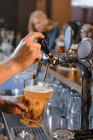 Photo pour Image recadrée de barman versant de la bière dans du verre au bar - image libre de droit