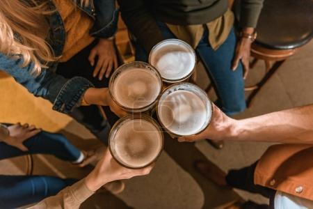 Photo pour Vue du dessus de la société cultivée tenant des verres avec de la bière au bar - image libre de droit