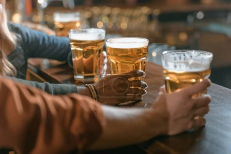 cropped image of company holding glasses with beer at bar