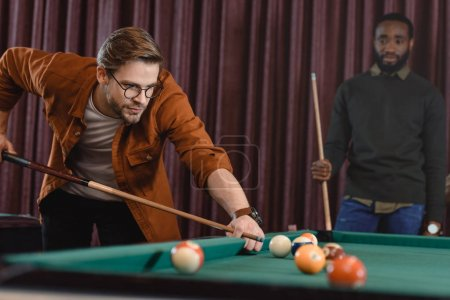 handsome man playing in pool at bar with friend