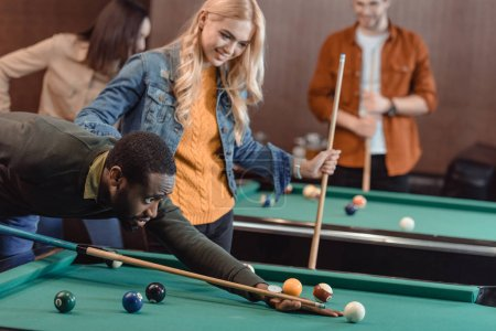young attractive multiculture friends playing in pool at bar