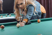 young beautiful caucasian woman playing in pool at bar