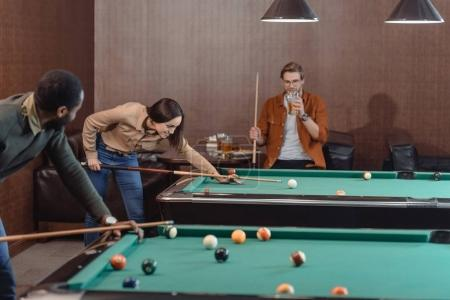 young successful multiculture friends playing in pool at bar