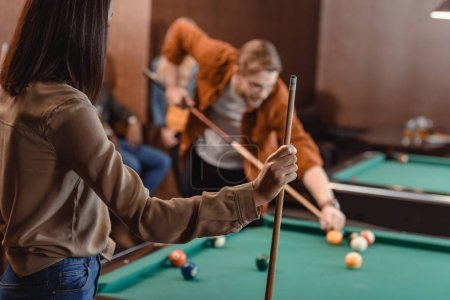 back view of girl with cue infront of gambling pool table