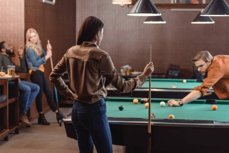 young successful multiethnic friends playing in pool at bar