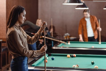 young girl chalking cue beside pool table at bar with friends