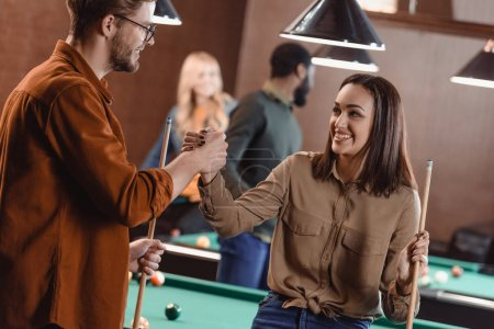 young attractive man and woman holding hands in pool bar with friends