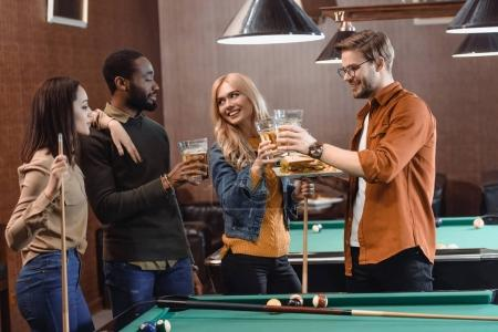 Photo for Company of multiethnic friends eating and drinking beside pool table at bar - Royalty Free Image