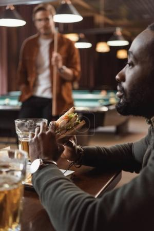 african amercian man eating sandwich at bar