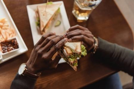 cropped image of african american man holding sandwich