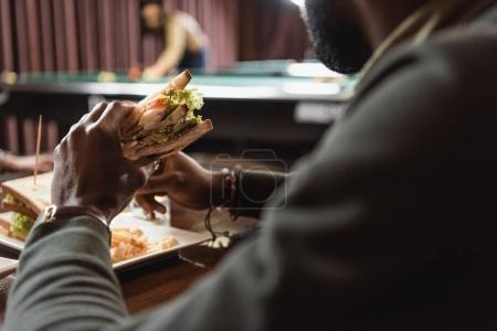 cropped image of african amercian man eating sandwich at bar