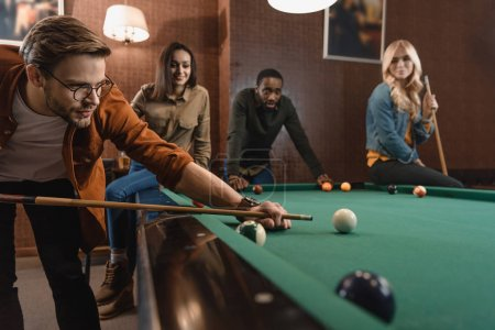 young attractive multiethnic friends playing in pool at bar