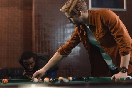 handsome multiethnic men playing in pool at bar