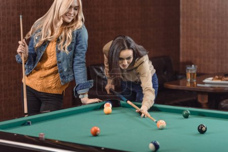 two young girls playing in pool at bar